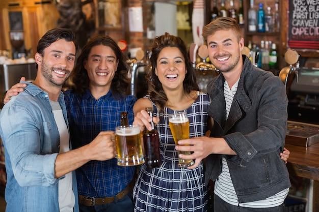 Portrait D'amis Jetant Des Verres à Bière Et Des Bouteilles Dans Un Pub Photo Premium