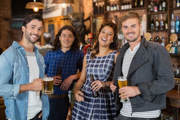 Portrait D'amis Tenant Des Verres à Bière Et Des Bouteilles Dans Un Pub Photo Premium