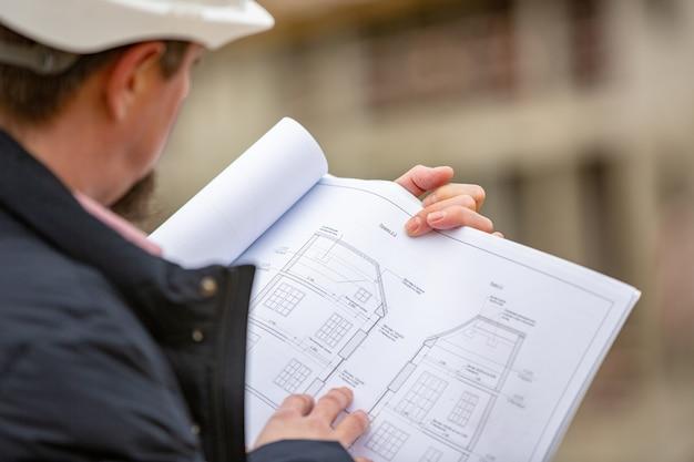 Portrait D'architecte Au Travail Avec Casque Dans Un Chantier De Construction, Lit Le Plan, Projets Papier Photo Premium