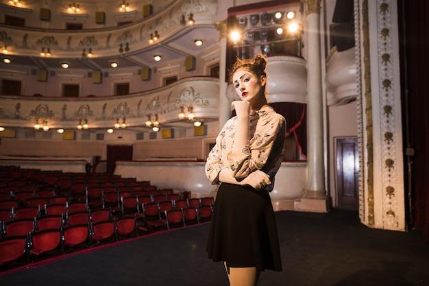 Portrait de l'artiste mime féminin réfléchie debout sur scène Photo gratuit