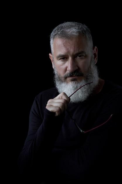 Portrait artistique d'un homme brutal aux cheveux gris avec une barbe et des lunettes sur fond noir, mise au point sélective Photo Premium