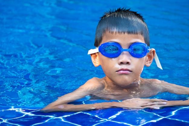 Portrait, asiatique, articles, bleu, lunettes, flotter, coin, piscine, bleu, rafraîchissant, eau Photo Premium