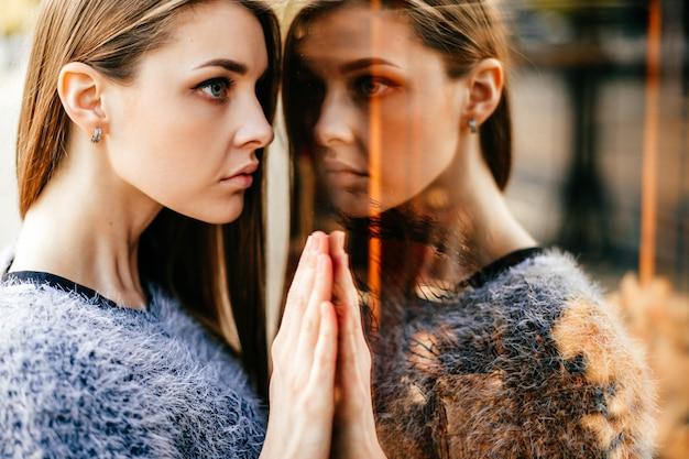 Portrait de l'auto-réflexion de la jeune fille étonnante dans la fenêtre en miroir Photo Premium