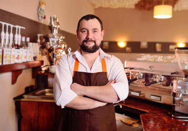 Portrait d'un beau barista masculin dans un tablier Photo Premium