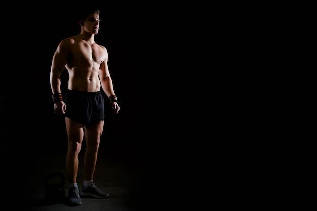 Portrait d'un beau bodybuilder musculaire avec un torse musclé dans le gymnase. Photo Premium