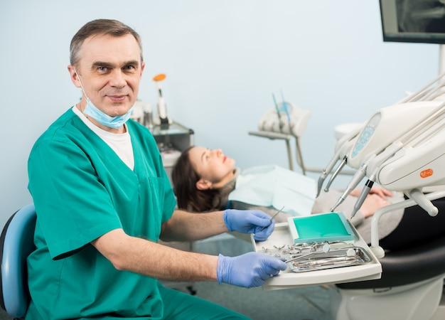 Portrait De Beau Dentiste Masculin Avec Des Appareils Dentaires Dans La Clinique Dentaire. Patiente. Dentisterie Photo Premium