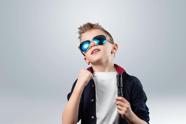 Portrait d'un beau garçon sur un fond gris. le garçon à lunettes noires. Photo Premium