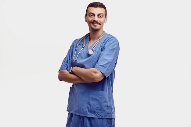 Portrait de beau jeune docteur arabe confiant avec moustache fantaisie en bleu isolé sur blanc Photo Premium