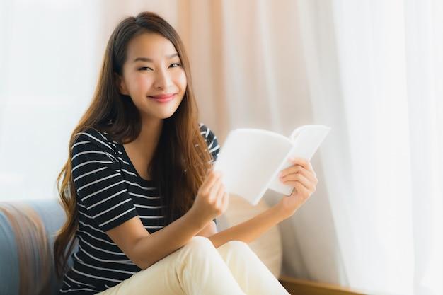 Portrait, beau, jeune femme asiatique, lecture, livre, sur, sofa, dans, salon Photo gratuit