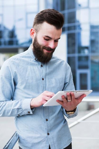 Portrait d'un beau jeune homme à l'aide de tablette numérique Photo gratuit