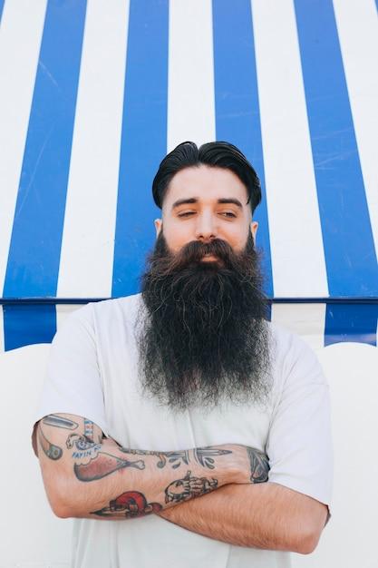 Portrait d'un beau jeune homme barbu avec un tatouage sur sa main Photo gratuit