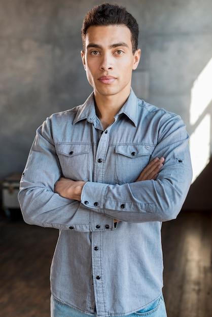 Portrait d'un beau jeune homme en chemise en jean avec les bras croisés en regardant la caméra Photo gratuit