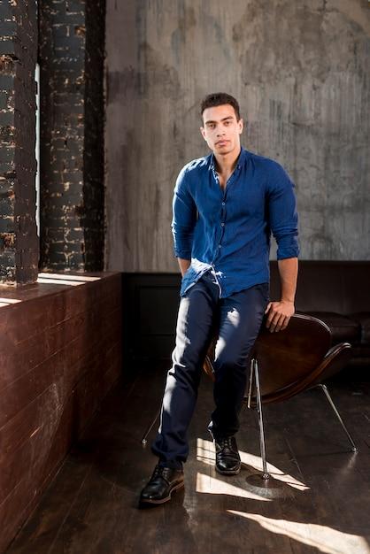 Portrait, beau, jeune homme, penchant, chaise, salle Photo gratuit