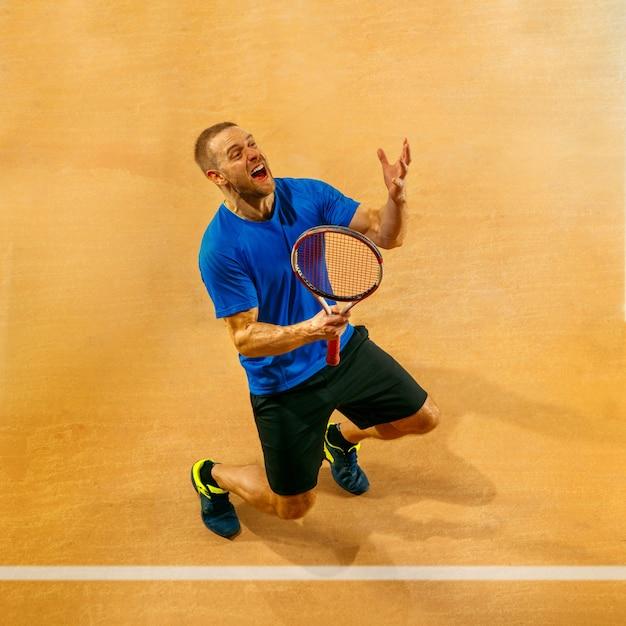 Portrait D'un Beau Joueur De Tennis Masculin Célébrant Son Succès Sur Un Mur De La Cour. émotions Humaines, Gagnant, Sport, Concept De Victoire Photo gratuit