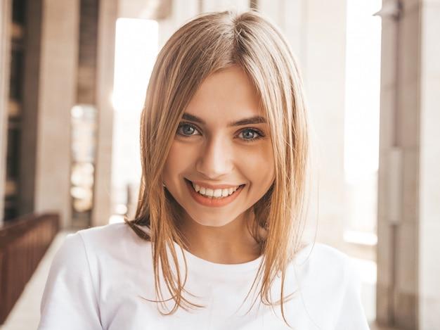 Portrait De Beau Modèle Blond Souriant Vêtu De Vêtements D'été Hipster. Fille Branchée Posant Dans Le Fond De La Rue. Femme Drôle Et Positive Photo gratuit