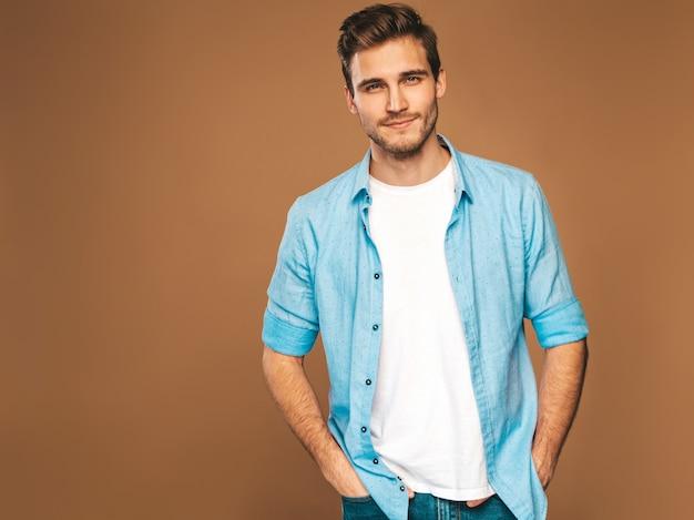 Portrait De Beau Modèle élégant Jeune Homme Souriant Vêtu De Vêtements Jeans. Homme De Mode. Posant Photo gratuit