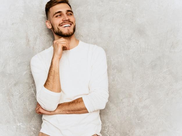 Portrait De Beau Modèle D'homme D'affaires Souriant Hipster Portant Des Vêtements Décontractés D'été Blanc .. Toucher Son Menton Photo gratuit