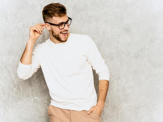 Portrait De Beau Modèle D'homme D'affaires Souriant Hipster Portant Des Vêtements Décontractés D'été Blanc. Photo gratuit