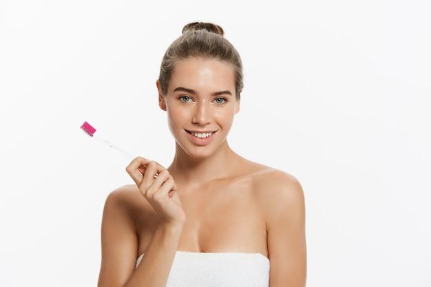 Portrait de beauté d'une belle femme à moitié nue heureuse se brosser les dents avec une brosse à dents Photo Premium