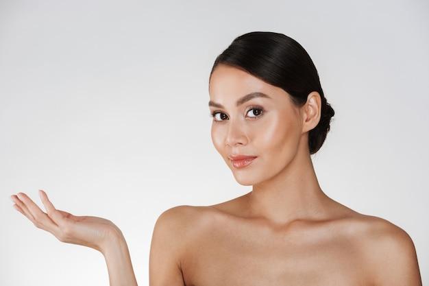 Portrait De Beauté De Charmante Femme Aux Cheveux Bruns En Chignon Regardant La Caméra Et Démontrant Quelque Chose Sur Sa Paume, Isolé Sur Blanc Photo gratuit