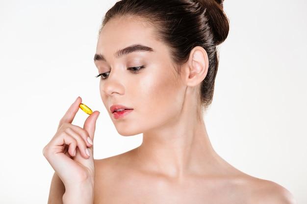 Portrait De Beauté D'une Femme Assez Concentrée Avec Une Peau Douce Tenant Une Pilule Dans Sa Main Posant Photo gratuit
