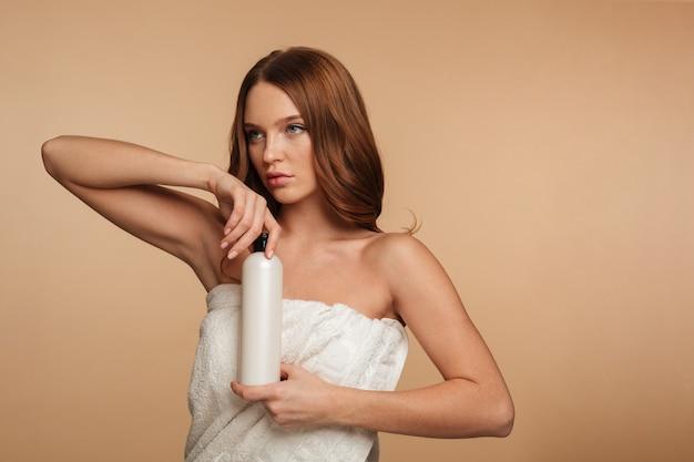 Portrait De Beauté De Femme Au Gingembre Aux Cheveux Longs Enveloppé Dans Une Serviette En Détournant Les Yeux Tout En Tenant Une Bouteille De Lotion Photo gratuit