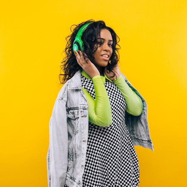 Portrait De Beauté De Jeune Fille Afro-américaine Avec Une Coiffure Afro. Fille Posant Sur Fond Jaune, Regardant La Caméra, Souriant. Prise De Vue En Studio. Photo Premium