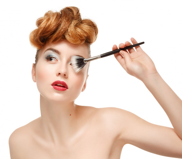 Portrait de beauté de jolie femme avec une brosse pour le maquillage Photo Premium