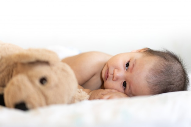 Portrait de bébé heureux se détendre sur le lit Photo Premium