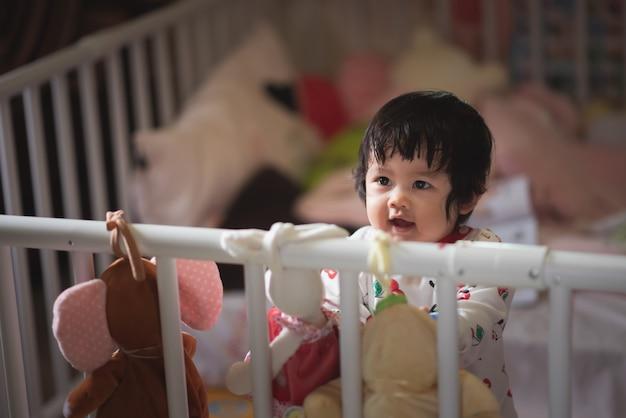Portrait De Bébé Mignon Dans La Barrière De L'enfant Photo Premium