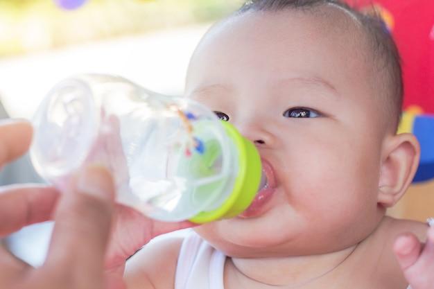 Portrait, de, bébé mignon, sur, voiture jouet, eau potable, de, bouteille Photo Premium
