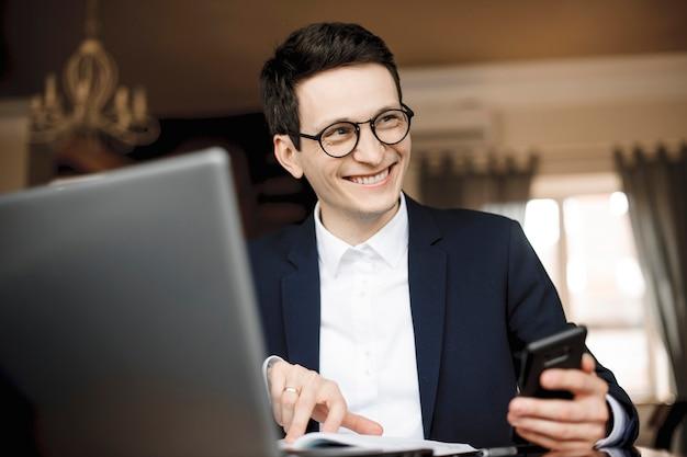 Portrait D'un Bel Homme D'affaires Confiant Travaillant Tout En Tenant Un Smartphone Et En Pointant Avec Le Doigt Dans Son Cahier à La Voiture En Riant Habillé En Costume. Photo Premium