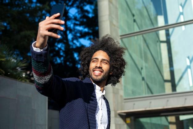 Portrait de bel homme afro-américain dans des vêtements décontractés à l'aide d'un téléphone portable et souriant tout en prenant un selfie, debout à l'extérieur de la ville Photo Premium