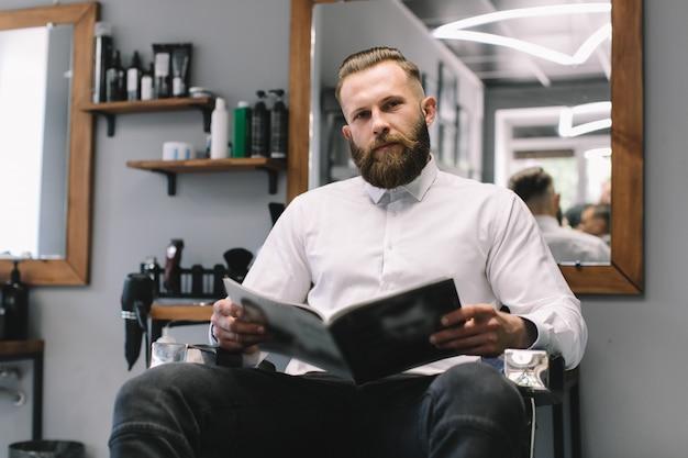 Portrait de bel homme barbu avec une coiffure à la mode et la barbe au salon de coiffure. Photo Premium