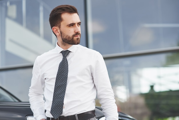Portrait D'un Bel Homme En Vêtements D'affaires Debout à L'extérieur Dans Le Bureau. Photo gratuit