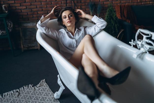 Portrait D'une Belle Brune Couchée Dans Une Salle De Bain Vide Tenant Les Jambes Photo Premium