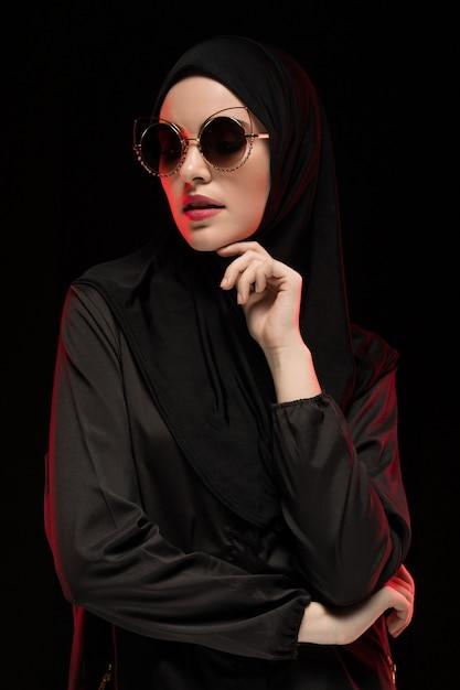 Portrait De La Belle élégante Jeune Femme Musulmane Portant Le Hijab Noir Et Des Lunettes De Soleil Comme Concept De Mode Orientale Moderne Posant Sur Fond Noir Photo Premium