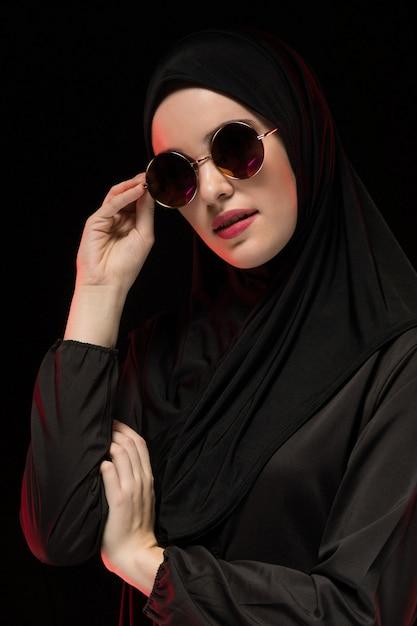 Portrait De La Belle élégante Jeune Femme Musulmane Portant Le Hijab Noir Et Des Lunettes De Soleil Comme Concept De Mode Orientale Moderne Posant Noir Photo Premium