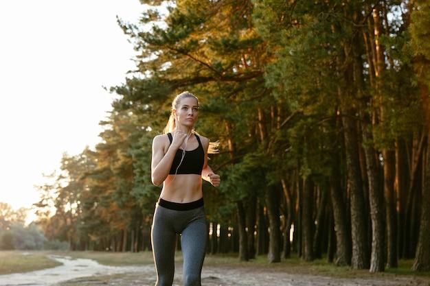Portrait de la belle femme active en casque de jogging dans le bois, écouter de la musique. Photo gratuit