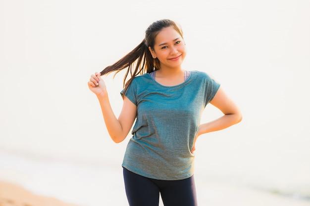 Portrait belle femme asiatique jeune sport courir et exercer sur la plage près de la mer et l'océan au lever ou coucher du soleil Photo gratuit