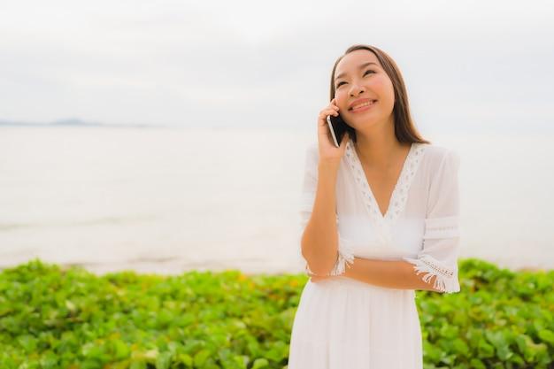 Portrait belle femme asiatique porter un chapeau avec le sourire heureux de parler de téléphone portable sur la plage Photo gratuit