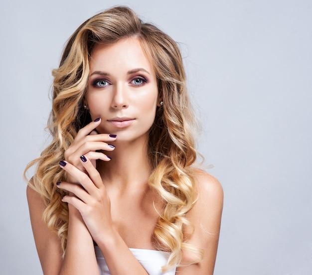 Portrait de belle femme blonde avec une coiffure frisée et maquillage lumineux. Photo Premium