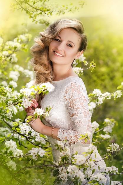 Portrait d'une belle femme blonde dans un jardin fleuri Photo Premium