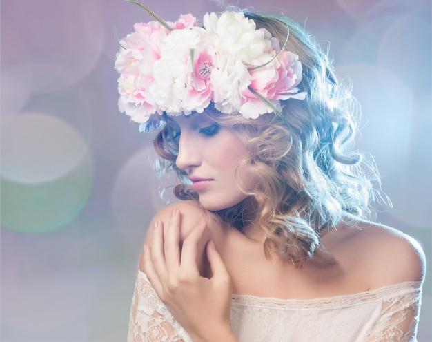 Portrait d'une belle femme blonde avec des fleurs dans les cheveux. Photo Premium