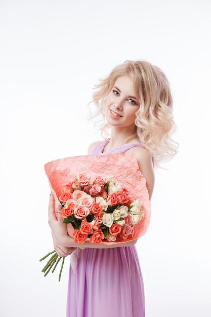 Portrait De La Belle Femme Blonde Frisée Avec Un Maquillage Parfait. Tenant Le Bouquet. Photo Premium