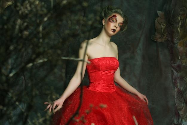 Portrait D'une Belle Femme Blonde En Robe Rouge. Maquillage Et Coiffure Créatifs. Tourné Dans Une Maison Fantastique. Photo Premium