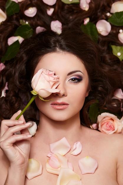 Portrait De La Belle Femme Brune Aux Longs Cheveux Bouclés Et Maquillage Lumineux Avec Des Fleurs Dans Les Cheveux Photo gratuit