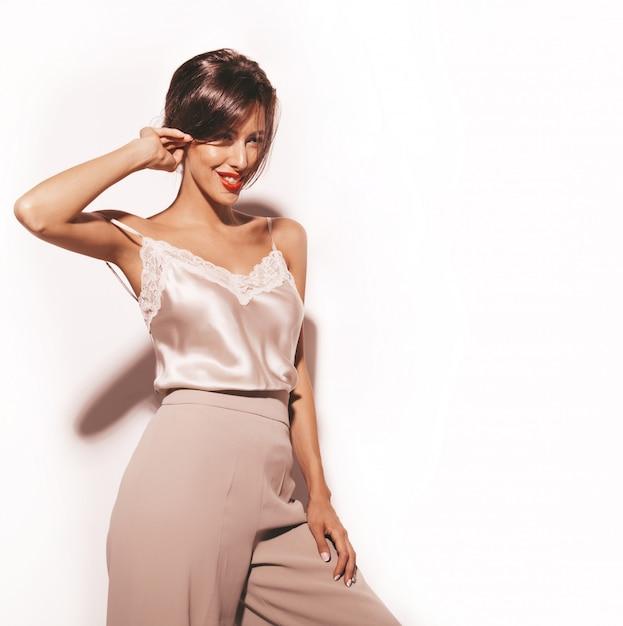 Portrait De La Belle Femme Brune Sensuelle. Fille En Vêtements Classiques Beiges élégants Et Pantalon Large. Modèle Isolé Sur Blanc Photo gratuit