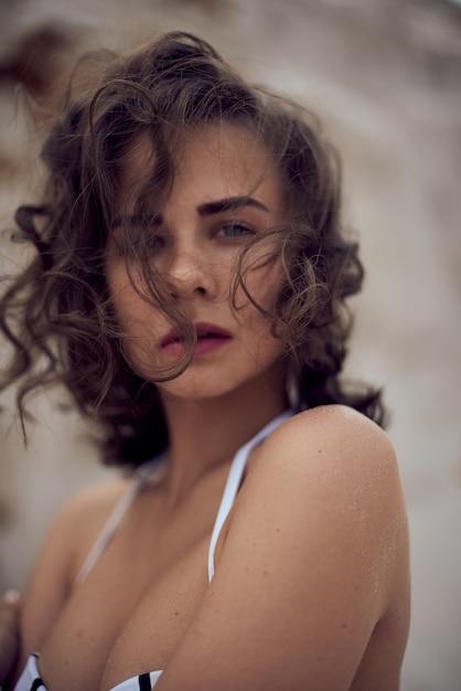 Portrait De La Belle Femme Caucasienne Bronzée Modèle Aux Cheveux Longs Noirs En Maillot De Bain Rayé Allongé Sur La Plage D'été Avec Du Sable Blanc. Vue De Dessus Photo Premium