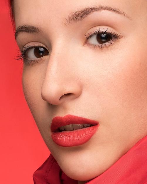 Portrait de belle femme sur fond rouge Photo gratuit